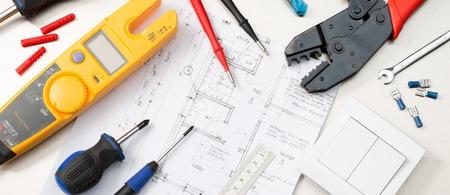 Formato di banner di sito Web di un assortimento di strumenti di appaltatori elettrici su piani di casa tra cui un multimetro, cacciaviti, trancianti e un interruttore della luce.