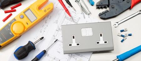 Webbanner-formaat opname van verschillende elektricienstools en componenten, waaronder een multimeter, schroevendraaiers, draadknippers, boren, schakelaars en stopcontacten.
