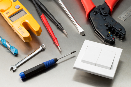 wirecutters: Various electrician tools and components including a multimeter, screwdrivers, wirecutters, drill bits and a light switch.