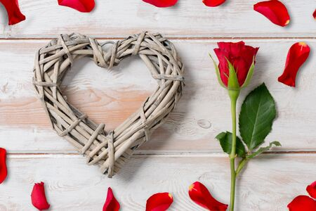 romatic: Rose and wicker rattan heart surrounded with rose petals on a wooden panel background for Valentines Day or other romatic occassions.