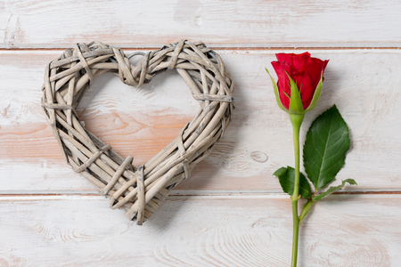 Rose and a heart-shaped wicker ornament on a wooden panel background for Valentines Day or other romatic occassions