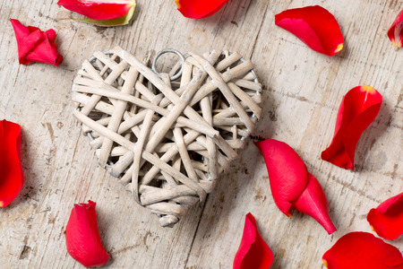 romatic: Close up of a heart-shaped weaved wicker decoration surrounded with red rose petals for Valentines Day and other romatic occassions.