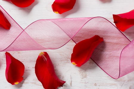 Close up of twirling purple chiffon ribbon and scattered rose petals on a wooden surface