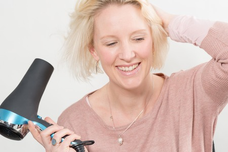 blow dryer: Blonde lady smiling while drying her hair with an electric blow dryer over a white background