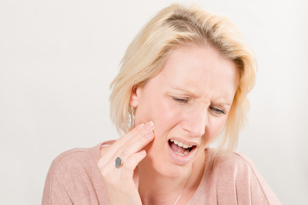 Blonde lady touching right cheek and in pain as if having a toothache, over a white background