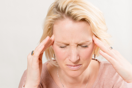 Blonde lady touches the side of her head with her fingertips with eyes closed as if having a severe headache with copy space.