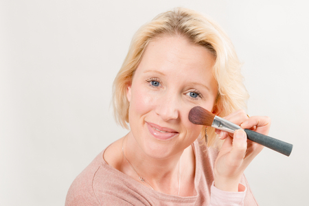 Blonde lady gazing directly while applying make-up on her cheek with a brush over white background