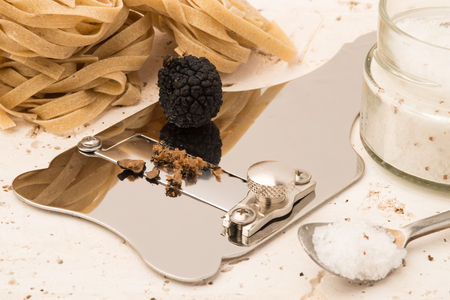 Steel truffle slicer with whole black truffle on top alongside a jar of salt, spoon, and raw pasta