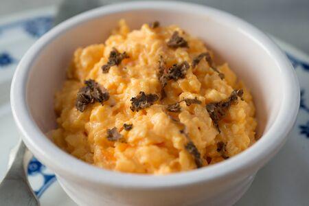 Closeup of a bowl of scrambled eggs with black truffle bits