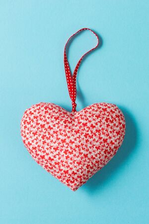 Overhead shot of a heart-shaped stuffed ornament over a green background for Valentines Day and similar occasions. Stock Photo
