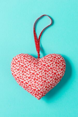 Overhead shot of a heart-shaped stuffed decor over a green background for Valentines Day and similar occasions.