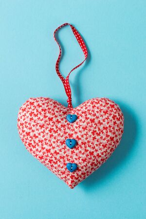 A buttoned heart-shaped stuffed decoration over a green background