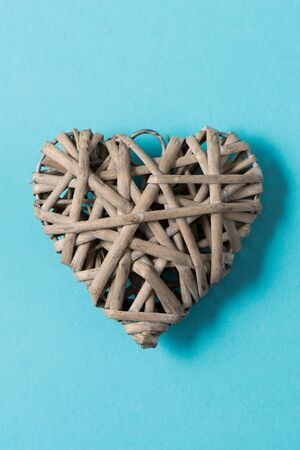 Woven wicker heart decoration over a green background for Valentines Day, Mothers Day, and similar holidays. Stock Photo