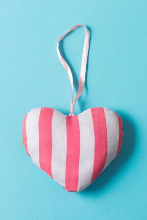 Stuffed heart-shaped ornament with pink and white striped design over a green background.
