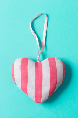 Pink and white striped stuffed heart trinket over a green background for Valentines Day, Mothers Day, and similar holidays.