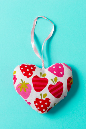 Heart-shaped stuffed trinket with strawberries design over green background