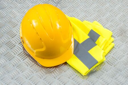 refle: Hard hat and a folded yellow safety vest on a steel checker plate