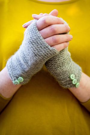 Hands wearing knitted woolen fingerless gloves