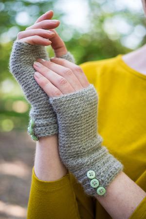 Hands wearing crocheted woolen fingerless gloves Stock Photo