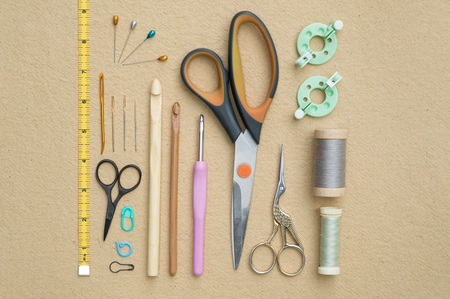 snips: Sewing and crocheting tools plus spools of thread and a tape measure arranged in order flat lay