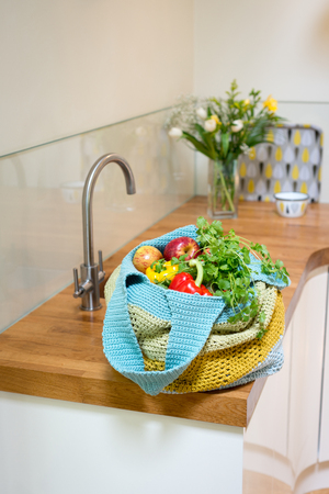Fruits and vegetables in a crocheted bag on a kitchen counter