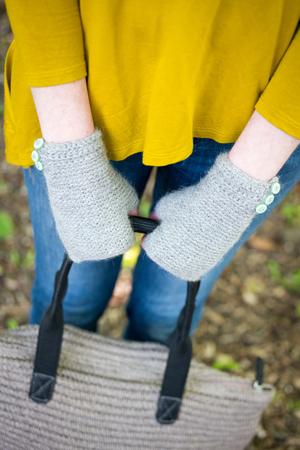 Hands wearing knitted fingerless gloves holding a woolen hand bag