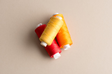 Spools of yellow, red and orange thread on an off-white background Stock Photo