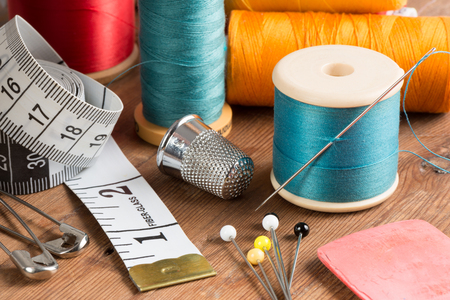 snips: Spools of thread and basic sewing tools including pins, needle, a thimble, and tape measure on a wooden tabletop
