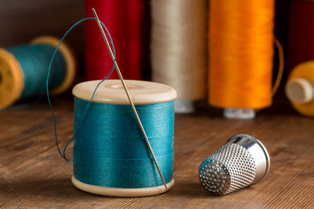 Spool of blue thread, a needle, and a thimble on a wooden table top with other spools of thread in the background