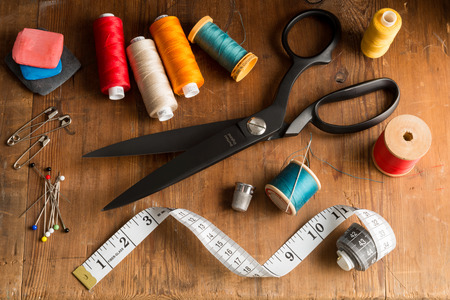 Sewing tools including fabric shears, tape measure, pins, tape measure, thimble, and tailors chalk and spools of different color thread on wooden tabletop Stock Photo