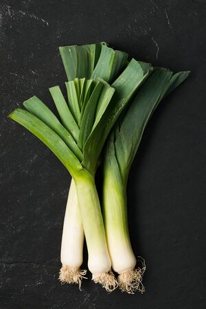 Three leek stalks on a dark grey stone surface Stock Photo