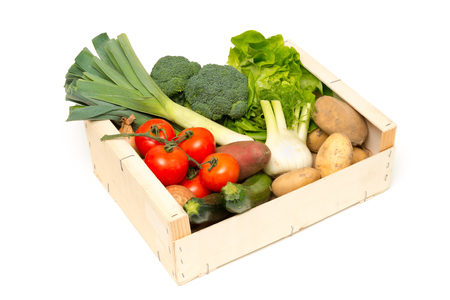 Variety of fresh ripe vegetables including leeks, broccoli, lettuce, tomatoes, sweet potatoes, zucchini, fennel, potatoes, and onions in a wooden box cut-out