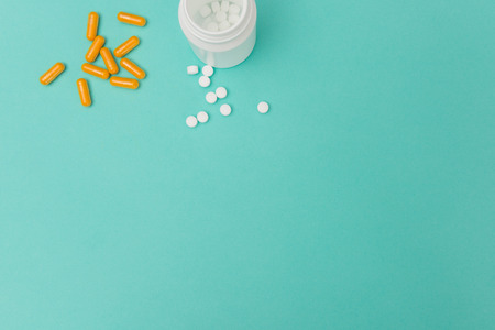 Orange-colored capsules, white pills, and an opened medicine bottle with copy space on a turquoise background