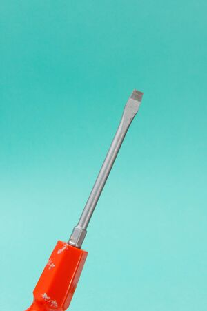 A flathead screwdriver over a turquoise background