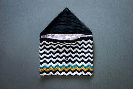 An Opened Crocheted Envelope Style Purse With Black And White