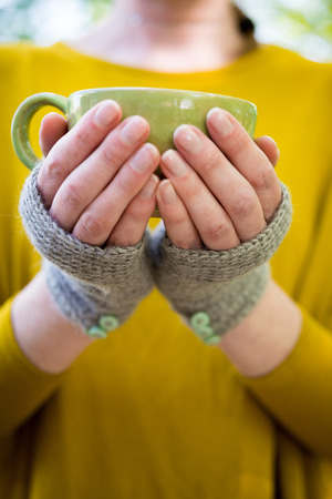 Hands in knitted fingerless gloves holding a cup