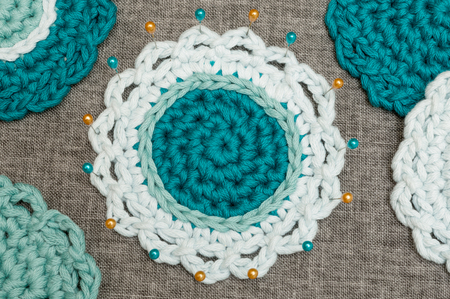 Round crocheted three-tone coaster in shades of blue fastened with straight pins surrounded by other crocheted coasters on muslin embroidery cloth Stock Photo