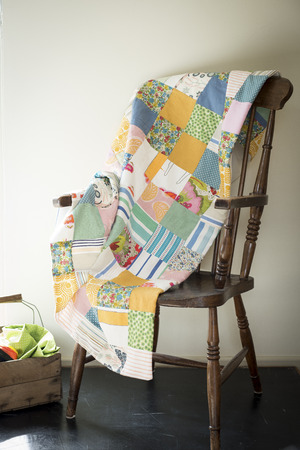 Multicolored patchwork blanket on an antique chair