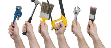 Hands facing left and holding various construction tools including a pipe wrench, hammer, paintbrush, hacksaw, an adjustable spanner, and a narrow paintbrush. Stock Photo