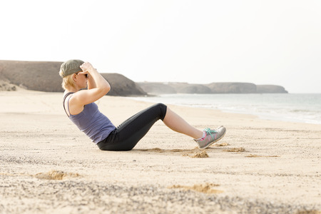 situp: Active woman doing sit-ups by the beach