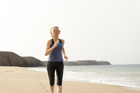 Fit woman in sportswear running in the beach with sea and hills in the background Stock Photo