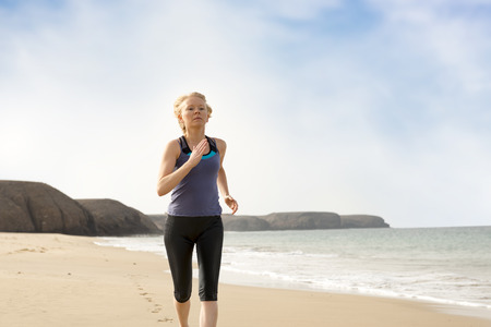 Active lady in sportswear jogging by the sea shore with sea, hills, and blue sky in the background