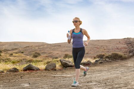 dirt: Active woman holding a bottle of water and running on dirt road