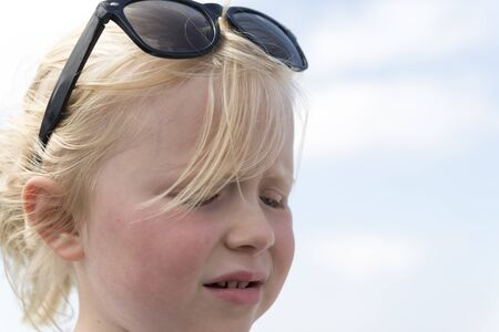 uneasy: Young girl with sunglasses looking below and seemingly worried