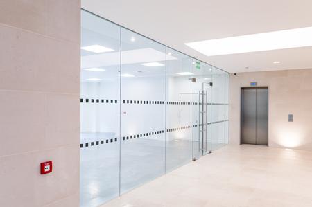 Glasaufteilung und Lift in leerem Arbeitsplatz Standard-Bild - 78224092