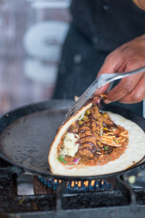 dosa: Folding an Indian dosa while cooking on a hot skillet