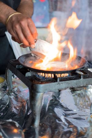dosa: Flames rising from a hot dosa skillet on stove