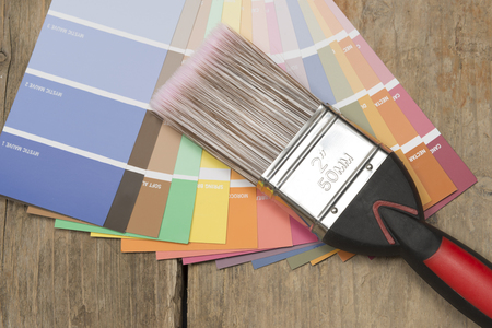 Overhead closeup of a paintbrush and various color paint swatches Stock Photo