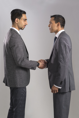 Two men in business suits shaking hands in a congratulatory manner