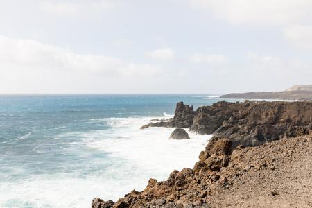 View along coast of rock formation and sea with crashing waves, Los Hervideros, Lanzarote Stock Photo